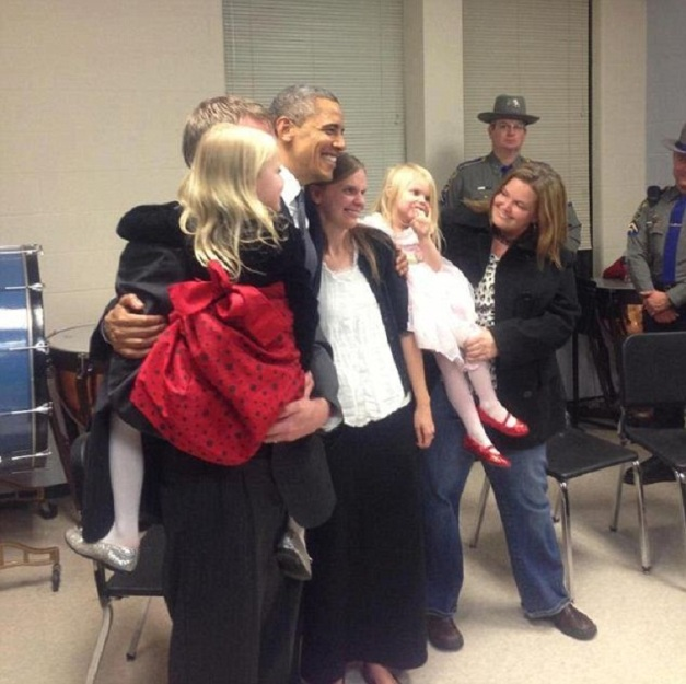 Las niñas con la madre posando con el presidente de los Estados Unidos entre sonrisas